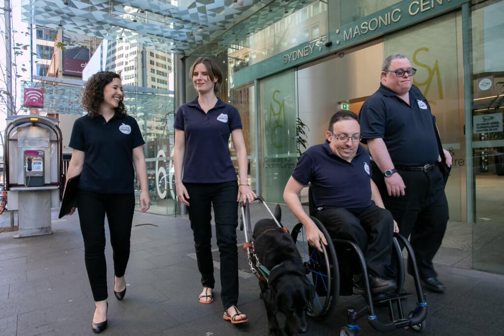 Group shot of Let's Talk Disability presenters walking along a city street